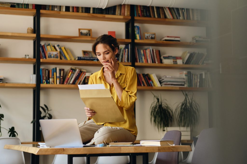 A customer in a home office holds an open envelope and reads its contents.